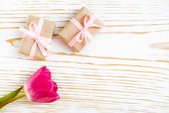 Pares del regalo envueltos con una cinta y un tulipán rosados en un fondo de madera blanco Imagenes de archivo
