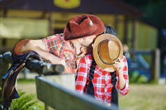 Pares del vaquero que besan un individuo y a una muchacha en sombreros de vaquero Fotos de archivo