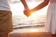 Pares del verano que llevan a cabo las manos en la puesta del sol en la playa Imagen de archivo libre de regalías