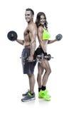 Pares deportivos jovenes de la aptitud hermosa con pesa de gimnasia Fotos de archivo libres de regalías