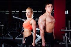 Pares deportivos jovenes hermosos que muestran el músculo y que presentan con pesas de gimnasia en gimnasio durante photoshooting fotos de archivo