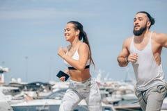 Pares deportivos jovenes que corren sobre el embarcadero de madera en la puesta del sol fotos de archivo libres de regalías