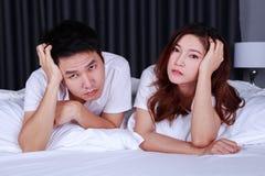 Pares deprimidos jovenes en cama en dormitorio Fotos de archivo
