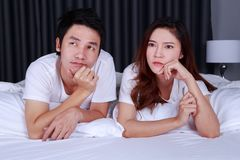 Pares deprimidos jovenes en cama en dormitorio Foto de archivo libre de regalías