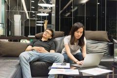 Pares deprimidos que trabajan tarde en sala de estar en la noche Foto de archivo libre de regalías