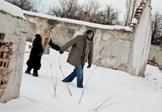Pares desabrigados que andam nas mãos da terra arrendada da neve Fotografia de Stock Royalty Free