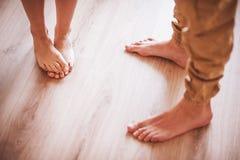 Pares descalzos que se colocan en piso de madera foto de archivo