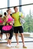Pares desportivos com garrafas de água e sacos no gym fotos de stock royalty free