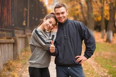 Pares desportivos felizes que abraçam delicadamente no parque do outono imagens de stock