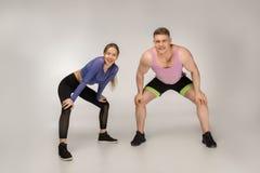 Pares desportivos novos no sportswear colorido que descansa após a formação fotos de stock