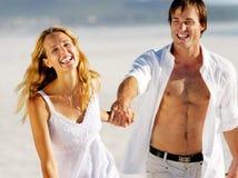 Pares despreocupados de la playa que recorren Foto de archivo libre de regalías