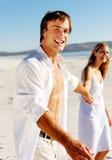 Pares despreocupados de la playa que recorren Imagen de archivo libre de regalías