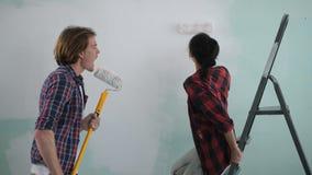 Pares despreocupados emocionados que tienen pared de la pintura de la diversión metrajes