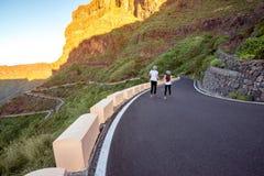 Pares despreocupados que correm na borda da estrada da montanha Fotos de Stock Royalty Free