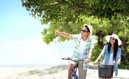 Pares despreocupados que tienen la diversión y bicicleta sonriente del montar a caballo en el bea Imágenes de archivo libres de regalías