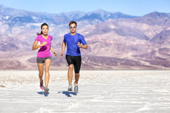 Pares determinados running que movimentam-se contra a montanha Fotos de Stock Royalty Free