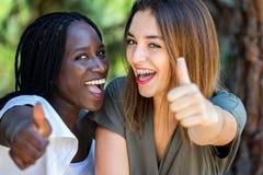 Pares diversos adolescentes felices que hacen los pulgares para arriba Foto de archivo