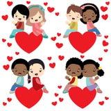 Pares diversos de los niños que se sientan en tarjeta del día de San Valentín de los corazones Imagenes de archivo