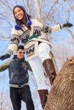 Pares diversos jovenes que caminan en un inicio de sesión la nieve en invierno Fotografía de archivo libre de regalías