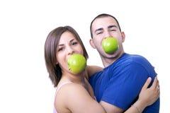 Pares divertidos con las manzanas en su boca Foto de archivo