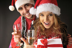 Pares divertidos de la Navidad con los vidrios de champán. Foto de archivo