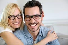 Pares divertidos en casa con las lentes Imagenes de archivo