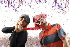 Pares divertidos que disfrutan de un partido del carnaval foto de archivo