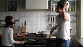 Pares divertidos que fingen la lucha o la guerra de la cocina que sostiene los utensilios almacen de video