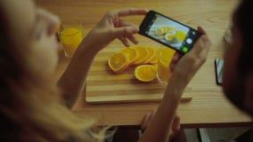 Pares divertidos que toman las imágenes de naranjas sabrosas en la cocina almacen de video
