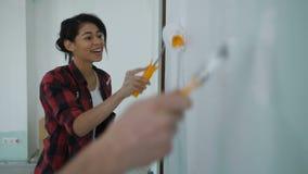 Pares diy felices que renuevan la nueva pared de pintura casera almacen de metraje de vídeo