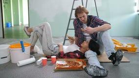 Pares diy felizes que relaxam após ter pintado uma sala video estoque