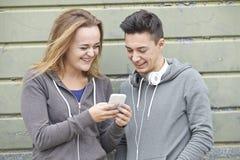 Pares do adolescente que compartilham da mensagem de texto no telefone celular fotografia de stock royalty free