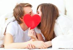 Pares do amante que beijam com um coração vermelho na cama imagens de stock royalty free