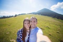 Pares do amor que caminham nas montanhas e para tomar o selfie na câmera imagens de stock royalty free