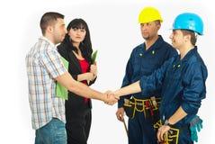Pares do aperto de mão com trabalhadores do construtor Fotos de Stock Royalty Free