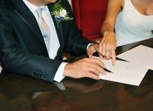 Pares do casamento durante a assinatura de seu contrato de união foto de stock