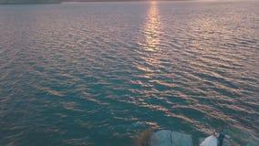 Pares do casamento junto na inclinação da montanha perto do mar Noivo e noiva bonitos Por do sol Tiro do ar filme