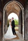 Pares do casamento na entrada da igreja Fotos de Stock Royalty Free