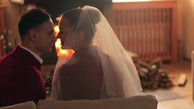 Pares do casamento no amor que aquece-se em camisetas vermelhas pela chaminé Os noivos relaxam e beijam pelo fogo morno e vídeos de arquivo