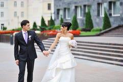 Pares do casamento que andam em uma cidade velha Fotos de Stock Royalty Free