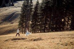 Pares do casamento que correm no campo Dia ensolarado nas montanhas Imagens de Stock Royalty Free