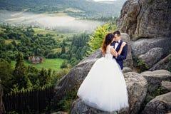 Pares do casamento que estão nas montanhas contra o céu R bonito Foto de Stock Royalty Free