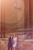 Pares do casamento que estão perto da parede Imagem de Stock Royalty Free