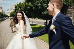 Pares do casamento que guardam as mãos de se na aleia do parque Fotos de Stock Royalty Free