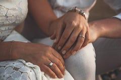 Pares do casamento que guardam as mãos no por do sol Anéis de casamento Homem que dá um anel de noivado a sua amiga imagens de stock royalty free