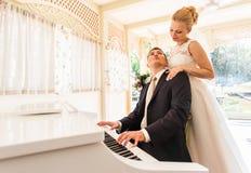 Pares do casamento que jogam em um piano na sala Foto de Stock Royalty Free