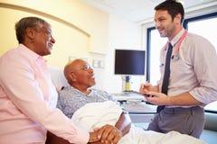Pares do doutor Talking To Senior na divisão Fotos de Stock Royalty Free