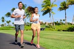 Pares do esporte que exercitam parte externa running na rua Fotos de Stock