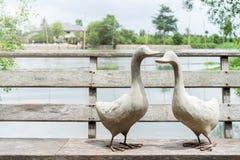 Pares do ganso branco que estão na ponte de madeira perto do rio, estátua de A do ganso dois no dia ensolarado imagem de stock