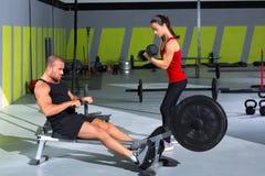 Pares do Gym com pesos do dumbbell e rower da aptidão foto de stock royalty free